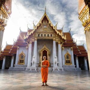 Buddhist monk standing in front of a temple in Bangkok Bangkok temple